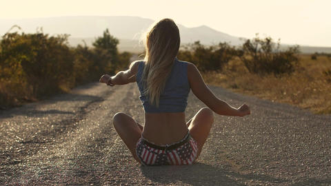 The image of a young woman on the road. She raises her hands like a bird spreads Live Action