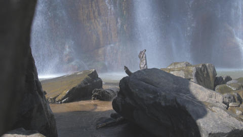 waterfall by wet stones appears from behind brown rock Live Action