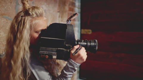 Young girl cinematographer shooting video by retro camera in brick studio. Girl Live Action