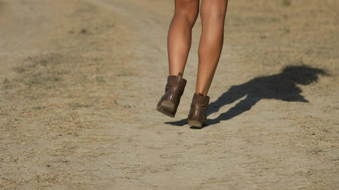 Beautiful female legs step on a dusty road Live Action