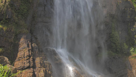 fresh water falls from high brown rocky cliff in sunlight Live Action