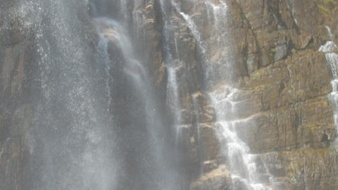 white foaming fresh water falls on wet brown rocks Live Action
