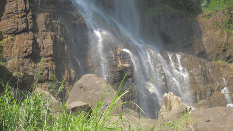 fresh water falls from high brown rocky cliff in sunlight Stock Video Footage