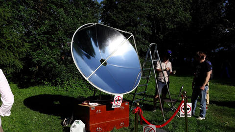 Sun lights reflector at fair show, green park environment, man give cooked piece Footage