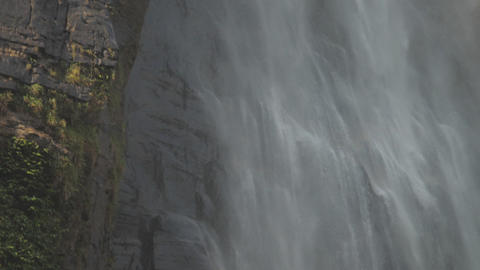 large waterfall surrounded by cliffs falls with water mist Live Action