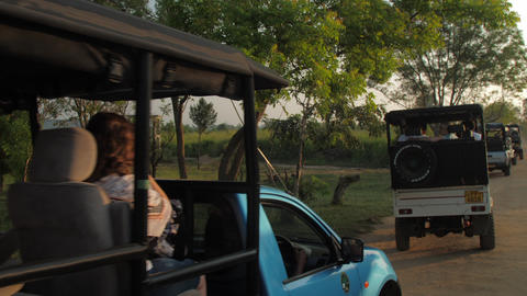 sport utility vehicles with tourists at brown ground road Live Action