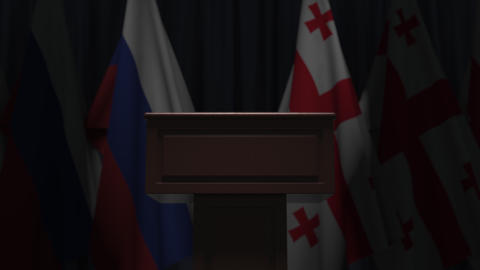 Flags of Russia and Georgia and speaker podium tribune. Political event or Live Action