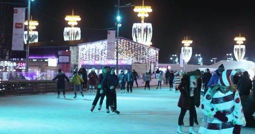 Skating rink visitors and stage and Christmas decoration on the background 실사 촬영