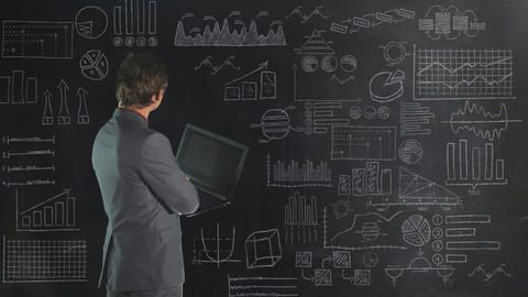 A man in front of a chalk board analyzes data from an infographic Live Action