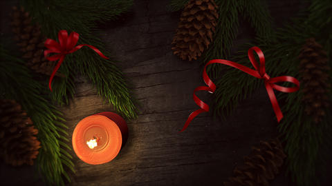 Animated closeup Christmas candle and green tree branches on wood background 애니메이션