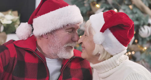 Close-up portrait of senior Caucasian couple rubbing noses, looking at camera Live Action
