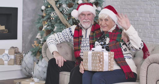 Medium shot, smiling old Caucasian man and woman sitting on couch with presents Live Action
