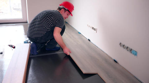 repair building and home concept. male worker installing wood flooring Live Action
