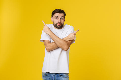 Handsome man over isolated yellow wall frustrated and pointing to the front Photo