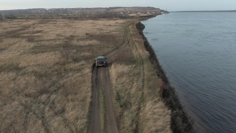 Black crossover car riding on sea shore along autumn field aerial view. Tourist off road suv car Live Action