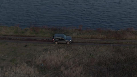 Black crossover car riding on river shore along autumn field aerial view. Tourist off road suv car Live Action