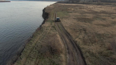 Crossover car riding on sea shore along autumn field aerial view. Tourist off road suv car driving Live Action