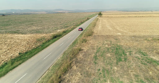 Car driving on a straight road Plan crops partially burned winter sunny aerial drone shot Live Action