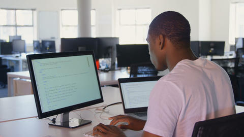 Rear view of young black male executive working desktop pc and laptop in modern office 4k Live Action