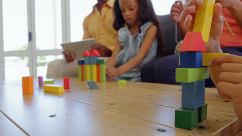 Children playing with building blocks on table in a comfortable home 4k Live Action