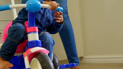 Front view of cute little black son playing and sitting on tricycle in a comfortable home 4k Live Action