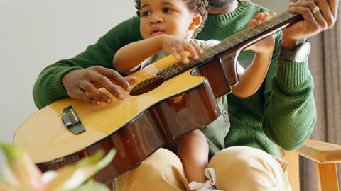 Front view of young black father and little son playing guitar in living room of comfortable home 4k Live Action