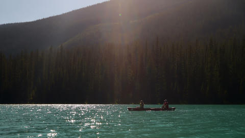 Side view of young couple rowing boat on a turquoise river in the sunshine 4k Live Action