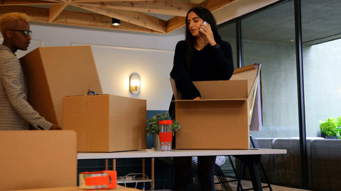 Front view of young mixed race business colleagues unpacking cardboard boxes in modern office 4k Live Action