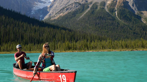 Front view of young couple rowing boat on a turquoise river in the sunshine 4k Live Action