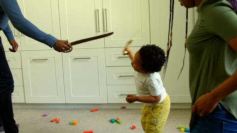 Side view of young black father and son playing with toy sword in a comfortable home 4k Live Action