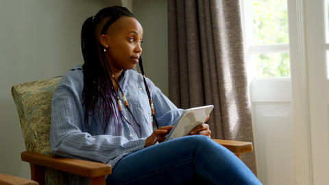 Side view of young black woman using digital tablet and sitting on the couch in comfortable home 4k Live Action