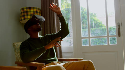 Front view of young black man using virtual reality headset in a comfortable home 4k Live Action