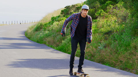 Front view of cool young caucasian skateboarders skating on downhill at countryside 4k Live Action