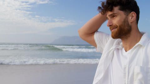 Side view of young caucasian man walking and looking around at beach on a sunny day 4k Live Action