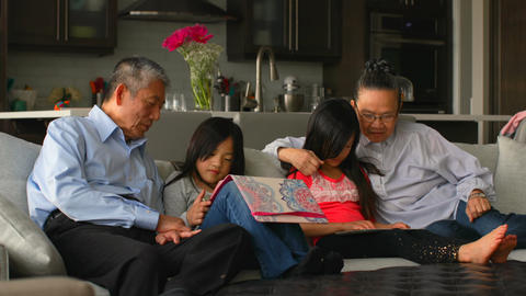Front view of multi-generation asian family using digital tablet in a comfortable home 4k Live Action