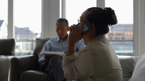 Side view of old senior asian woman talking on mobile phone in a comfortable home 4k Live Action
