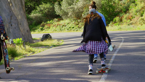 Rear view of cool young caucasian male skateboarders walking with skateboard at countryside road 4 4 Live Action