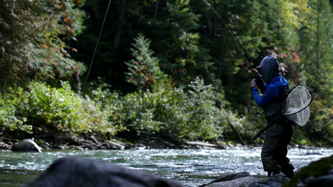 Side view of fisherman fishing in the forest stream on a bright sunny day 4k Live Action