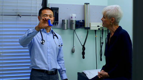 Young Asian male doctor and senior patient discussing over asthma inhaler at clinic 4k Live Action