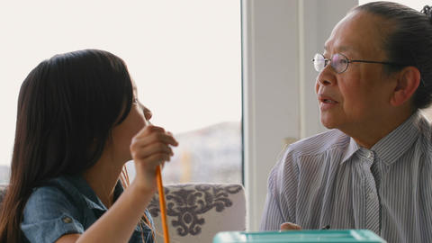 Front view of cute asian granddaughter and old grandmother interacting with each other at home 4k Live Action
