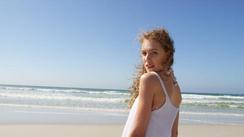 Woman standing at beach on a sunny day 4k Live Action