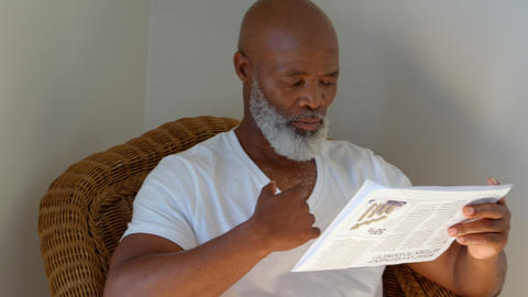 Front view of black mature man reading newspaper at home 4k Live Action