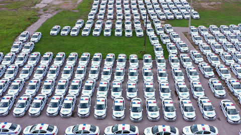 Drone top view many traffic police cars standing on parking. Same police patrol cars on parking lot Live Action