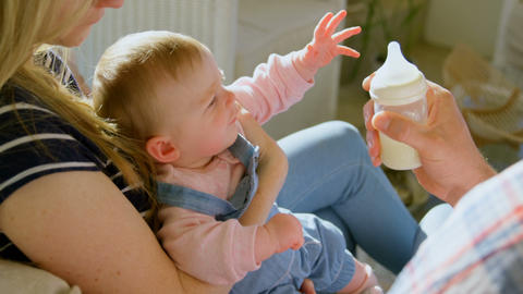 Mid adult caucasian parents feeding milk her baby from bottle in a comfortable home 4k Live Action