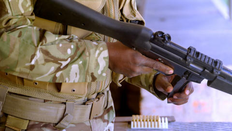 Mid section of black military soldier loading weapon during military training 4k Live Action