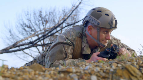 Side view of military soldier looking through binoculars during military training 4k Live Action