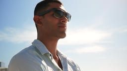 Man with sunglasses standing on the beach in sunshine 4k Live Action