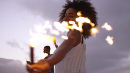 Couple dancing with sparklers on beach at dusk 4k Live Action