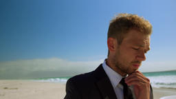 Businessman with hand on chin standing on beach in the sunshine 4k Live Action