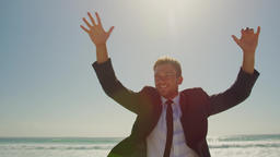 Businessman dancing on beach in the sunshine 4k Live Action